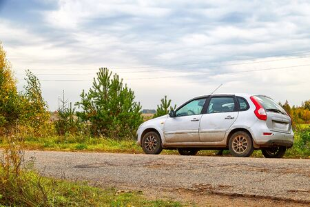 Car on a gravel dirt road next to green bushes and grass and under a sky with clouds. Natural road trip concept in autumn or summer day