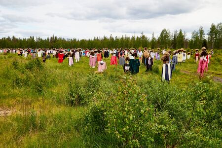 SUOMUSSALMI, FINLAND - JULY 24, 2019: View to the group of objects in people clothes which looks like crowd in the field in a summer or autumn day. Finland. Installation Reijo Kela Silent People