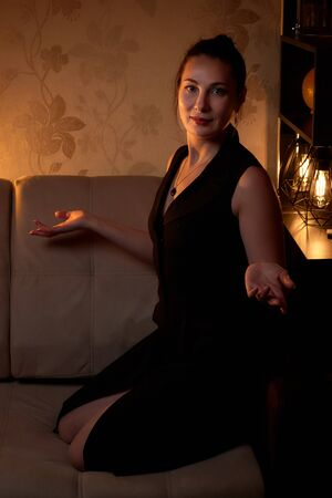 Elegant pretty middle aged woman with nice lamp with yellow light at the dark room