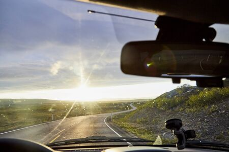 View on yellow sunset and clouds from the car front window and the glare on the glass. Driving car during sunshine in the tundra in Norway. Background of nature landscape and grey road