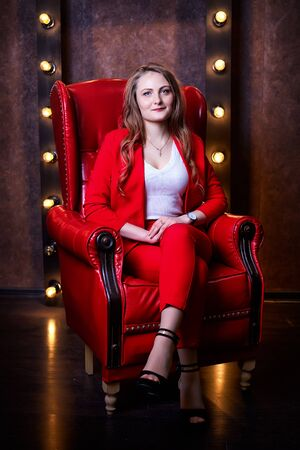 Girl in red costume sitting in red chair in the dark room. Model posing during fashion photoshoot