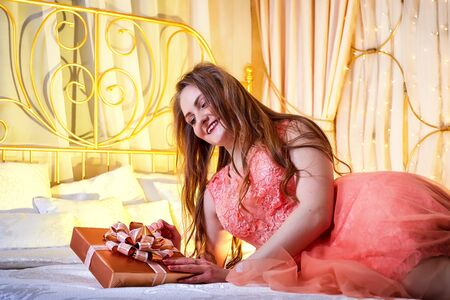 Girl in pink dress with present in the box on the bed with white linen. Model posing during fashion photoshoot