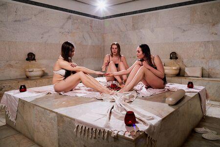 Three beautiful girls in turkish spa bath hamam. Woman in sauna at the spa zone. The concept of health and pleasure
