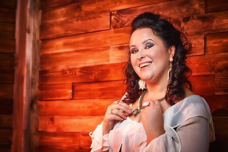 Portrait of fat plump fun charming cute woman with black curly hair in the room with hay and straw. Model posing during photoshoot in studio as like a country girl or a peasant girl