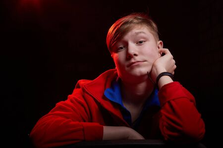 Low key portrait of a handsome brunette young male teenager in sweatshirt or hoodie. Interesting boy and dark background with blue light. Model posing during photoshoot 版權商用圖片
