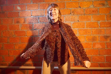 A middle-aged woman poses showing clothes near red brick wall. An inept model in non-professional shooting. Photography for sales short cardigan on the Internet or online store Stock Photo