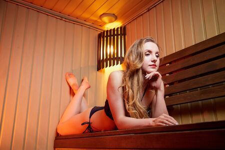 Beautiful girl on wooden bench at sauna in steam room with nice red and yellow light