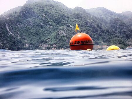 Sea surface with buoys with words No swimming and mountains in the distance. View and shooting from water in a summer day