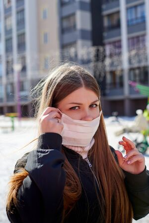 Beautiful young woman with long hair in spring clothes on the street with white medical mask on. Protect of a girl against infection with coronavirus Covid19 in Russia in russian city