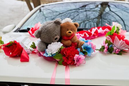 Wedding decoration on the car with ribbons, flowers and toys before marriage ceremony in Russia in a day