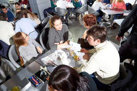 Kirov, Russia - September 25, 2019: People at table in small cafe or restaurant during intellectual game. Hungry group waiting for the waiter to get the menu or food