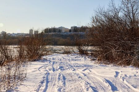 Small road or footpath covered by snow and city background in winter. Snow track from car in forest lanscape going to big houses far away in a cold day