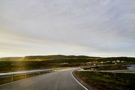 Landscape with road in tundra in Norway at cloudy evening in a summer, spring or autumn day