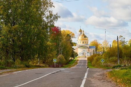 Asphalt road leading to the village with a beautiful white stone Orthodox Church with a yellow dome among nature and green trees. Natural landscape with greenery on summer, autumn or spring sunny day