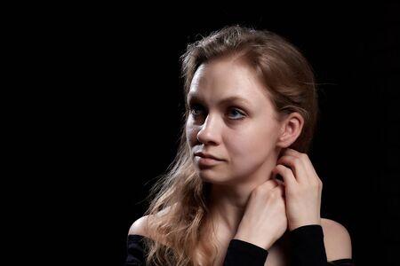 Beautiful gentle girl with long blonde hair on a dark background. Romantic portrait in Renaissance style Reklamní fotografie