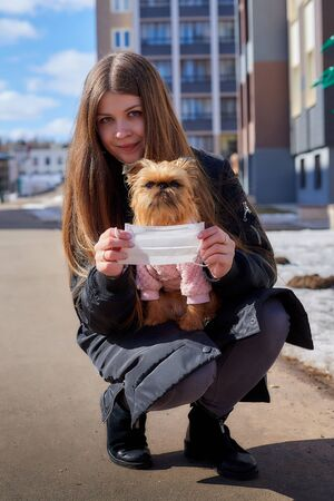 Girl trying to protect small dog from a coronavirus with a medical gauze white mask on the street in sunny spring day. Protection against disease during epidemics and pandemics. Covid-19 in Russia