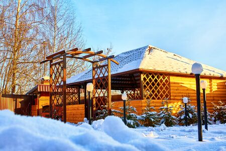 Yellow wooden gazebo in the yard on a Sunny winter day with blue sky