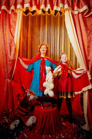 Family during a stylized theatrical circus photo shoot in beautiful red location. Models grandmother and granddaughter posing on stage with curtain