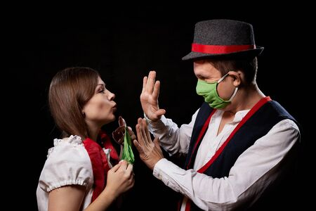 Couple in national traditional ethnic dress in green sterile medical face masks on a black background. Girl traying to kiss man during quarantine of COVID-19 coronavirus pandemic. Concept of isolation