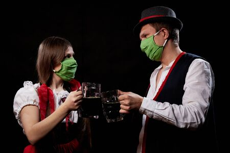 Couple in national traditional ethnic dress in green medical face masks with beer on black background. Girl and man drinking beer in COVID-19 coronavirus pandemic. Oktoberfest during the virus period