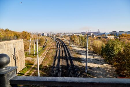 View on railway from high place and trees arround in a summer or autumn day. Nice lanscape with city and nature