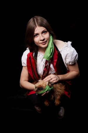 Girl in a protective medical green mask and national ethnic dress holding small dog in her hands. Coronavirus, COVID-19 pandemic concept. Domestic animal allergy, sneezing and coughing near of pets