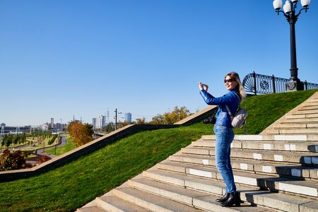 Attractive beautiful young girl holding cell phone in autumn park and making selfie. Female photographer traveller on the steps
