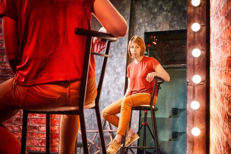 Girl in red shirt on a tall chair in front of a lighted mirror in a dark room. Model posing for a cam during photoshoot in the Studio