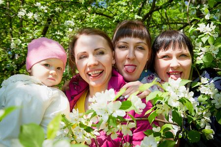 Three different funny women and one small seriously girl in the park full of apple blossom trees in a spring day. Aunts and niece in green nature landscape