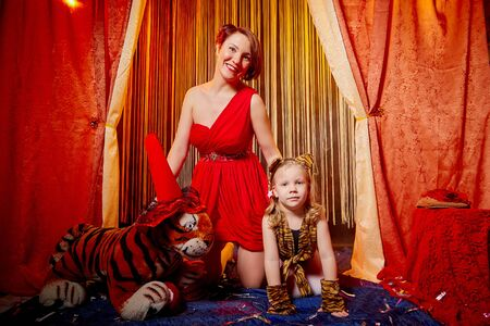 Family during a stylized theatrical circus photoshoot in a beautiful red location. Models a mother who looks like a trainer and a daughter who looks like a tiger pose on stage with curtains
