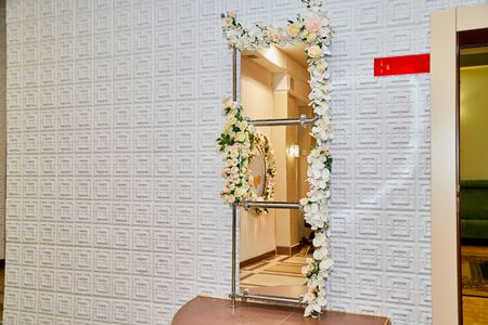 Mirror with white flowers near the wall in the room