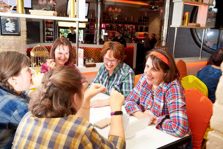 Kirov, Russia - October, 2019: People at table in small cafe or restaurant during intellectual game. People waiting for the waiter to get the menu or food Редакционное