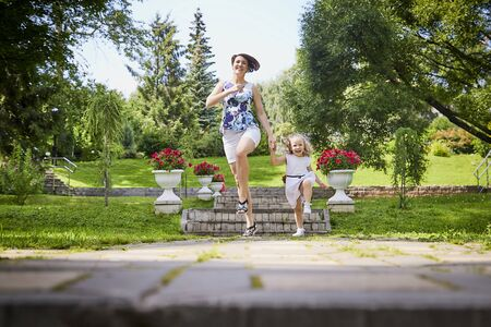 Happy mother and daughter in the park. Family resting and having fun outdoor. Beauty nature scene with family outdoor lifestyle. 写真素材