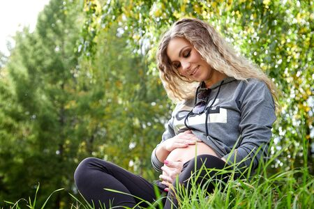 Beautiful pregnant woman relaxing in green park in a summer day. The concept of a healthy pregnancy and a healthy lifestyle