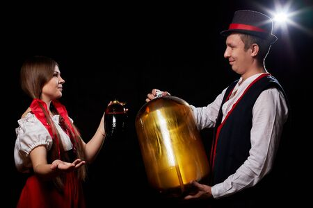 Happy Oktoberfest couple in national ethnic dress with kegs of beer on a black background. Girl and boy having fun posing in studio with alcohol during celebration Oktoberfest 免版税图像
