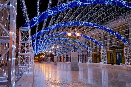 Decorated Christmas tunnel and ice rink in the night street of the city. Nobody outdoor in dark evening time