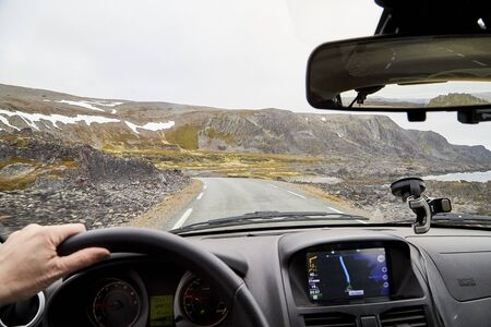 View from car window on the road and pity strange landscape with a mountains, rocks and cloudy sky and hand of woman. Landscape through windscreen in Norway. Single trip for isolation in a coronavirus Banco de Imagens
