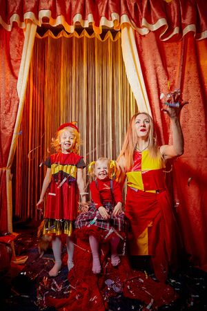 Family with dog during stylized theatrical circus photo shoot in a beautiful red location. Model mother and young daughters with small animal posing on stage with curtain