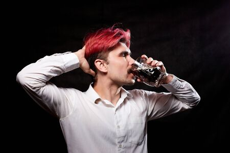 Young handsome guy with red hair in white shirt drinking beer and black background. Funny man with sad emotions on the face and a beer mug in hand. alcoholic with alcohol. Model in photoshoot