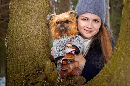 Girl with long hair in black jacket and grey hat posing with a small dog Brussels Griffon in clothes near big trunk in the forest or park in a winter day. 写真素材