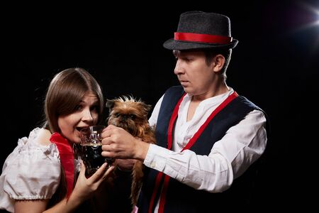 Happy Oktoberfest couple in national ethnic dress with mug of beer, small shaggy dog on black background. Girl and boy with pet Brussels Griffon having fun with alcohol during celebration Oktoberfest 写真素材