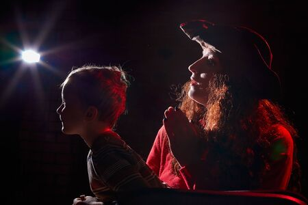 Ugle woman in red sweater and pirate hat with curly hair posing with small boy on black background. Actress mother and actor son in magical, fantastic, fairy-tale movie in dark studio and flash