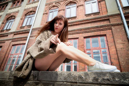 Brunette girl near near the facade of a large red brick building with windows in the Central part of the ancient city. Walk in downtown. Portrait of a funny pretty girl on the street of the town