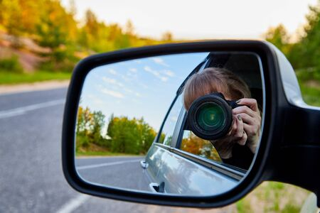 Car Mirror and reflection of traveller photographer and sky in it Imagens