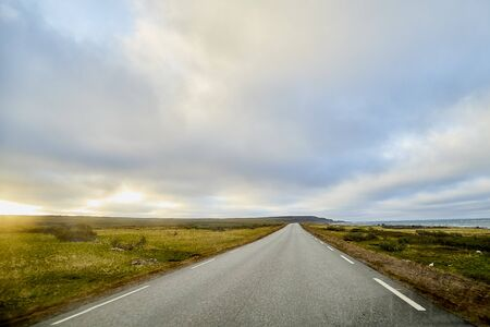 Landscape with road in tundra in Norway at cloudy evening in a summer, spring or autumn day Imagens
