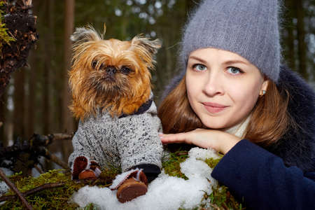 Girl with long hair in black jacket and grey hat posing with a small dog Brussels Griffon in clothes in the forest or park in a winter day