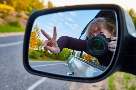 Car Mirror and reflection of traveller photographer and sky in it