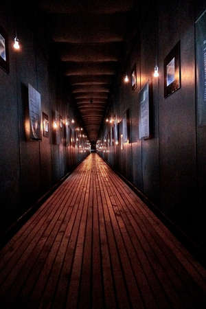 Vardo, Norway - 23 June 2019: Memorial devoted to memory innocently killed during witch hunting. Long dark narrow corridor with light from lamps and signs about executed and burned at stake women