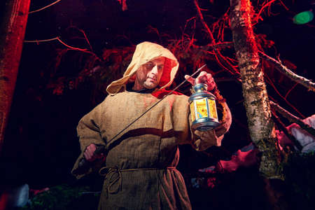 Medieval monk in canvas sackcloth robe with sword and lattern in dark forest and red light of moon on winter night. Fantasy or fairy tale about wandering monk. Concept of forces of good and evil