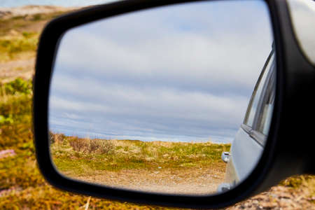 Car Mirror and reflection of tundra and sky in it